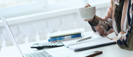 Morning coffee before a productive working day. Young female office worker holding coffee cup and looking at the laptop screen while sitting at her working place in office. Zdjęcie Seryjne