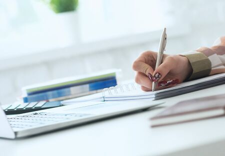 Hands of female financial manager taking notes when working on report. Businesswoman makes thoughts records at personal organizer, white collar conference.