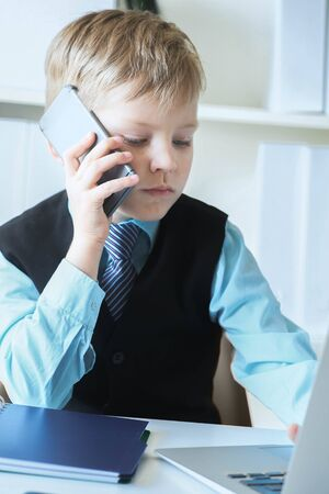Young confident executive businessman boss boy in office talks on the phone sitting at the desk with laptop. Stockfoto
