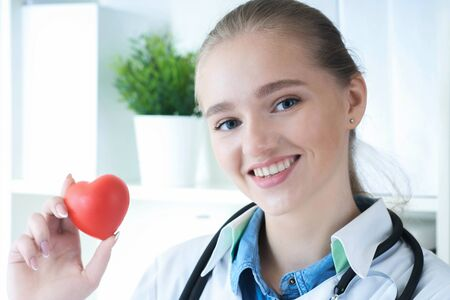 Beautiful Caucasian smiling female doctor hold in arms red toy heart closeup. Cardio therapeutist student education CPR life save. Physician make cardiac physical pulse rate measure arrhythmia