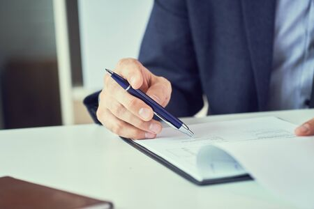 Businessman reading rental contract before making a deal. Corporate man with pen in hand working in modern office, signing business document on desk. close up. Banque d'images