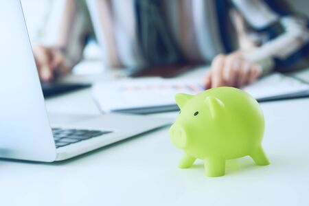 Womans hand pointing on summary report chart and calculate finance in office close-up. Calculator, green Piggy Bank, Laptop, business chart and graph document on desk. Debt.