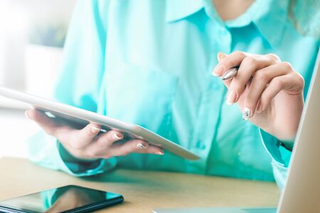 Business woman looking and studying statistics on tablet display closeup. Female left hand holds pen, right holds tablet. Stock fotó
