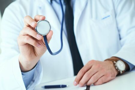 Close up of a doctors hand, holding a stethoscope outstretched towards the viewer. Medic shop or store, physical and disease prevention, er consultant, 911, pulse measure, healthy lifestyle concept Фото со стока