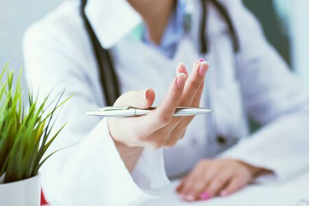 Female doctor explaining patient symptoms or asking a question as they discuss together in a consultation. Just hands over the table.