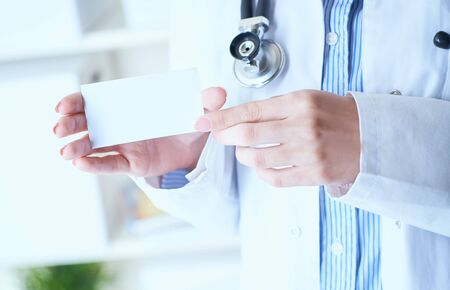Close-up image of female doctor with stethoscope and blank visiting card with place for text in hands.