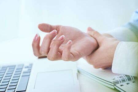 Young woman holding her wrist close-up . Pain from using computer. Office syndrome hand pain by occupational disease.