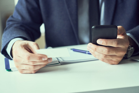 Businessman holding blank business card and dialing numbers on mobile phone Imagens