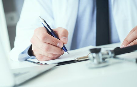 Mittlerer Abschnitt des männlichen Arztschreibens schreibt dem Patienten am Arbeitstisch ein Rezept. Allheilmittel und lebensrettende, verschreibende Behandlung.