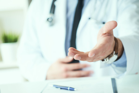 Male doctor making welcome gesture, politely inviting patient to sit down in medical office. Photo with depth of field.