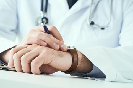 Homme médecin avec stéthoscope regardant montre-bracelet. Médecin en uniforme blanc au fond du bureau en attente de patients. Il est temps de consulter un thérapeute.
