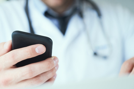 Male doctor hands with mobile phone close-up. Male doctor in white coat is using a modern smartphone device with touch screen.