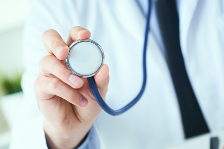 Close up of a doctors hand, holding a stethoscope outstretched towards the viewer. Medic shop or store, physical and disease prevention, er consultant, 911, pulse measure, healthy lifestyle concept Stock fotó