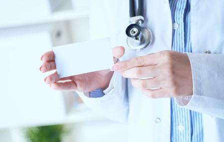 Imagen de primer plano de la doctora con estetoscopio y tarjeta de visita en blanco con lugar para el texto en las manos.