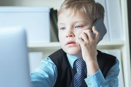 Young confident executive businessman boss boy in office talks on the phone sitting at the desk with laptop.