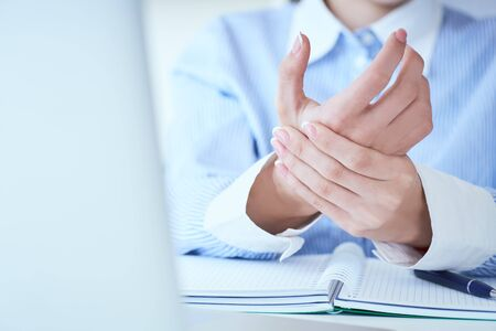 Junge Frau, die ihre Handgelenknahaufnahme hält. Schmerzen durch die Verwendung des Computers.