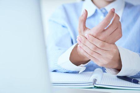 Młoda kobieta trzyma jej zbliżenie nadgarstka. Ból związany z używaniem komputera.