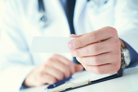 Male physician hand holding and giving white blank calling card closeup in office. Contact information exchange, introducing gesture at formal meeting, personal or family doctor concept Stock Photo