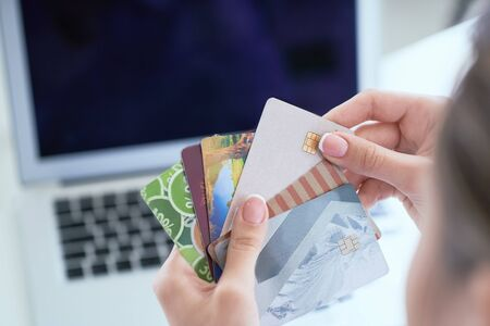 Woman hand holding various credit cards in order to make a purchase in the online store using a laptop.