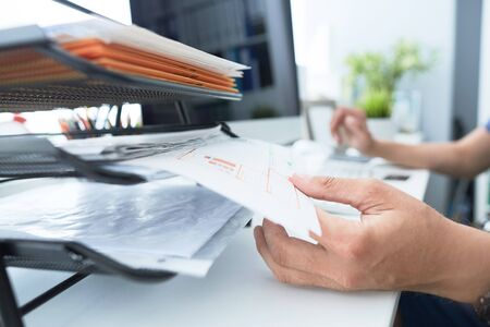 Close-up of young mans hand pulling files from office shelves.