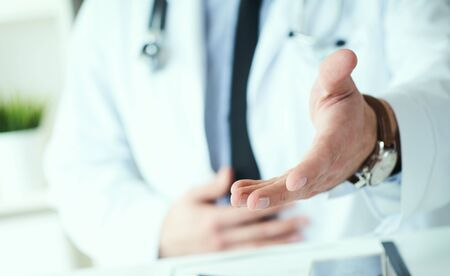 Male doctor making welcome gesture, politely inviting patient to sit down in medical office. Photo with depth of field. Just hands over the table. Banco de Imagens