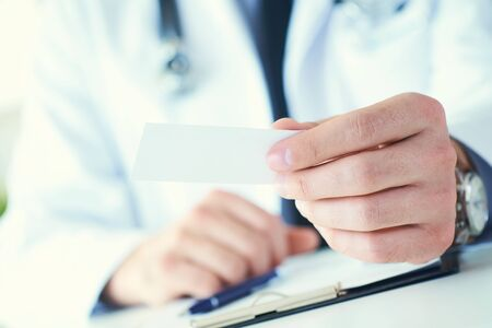 Male physician hand giving white blank calling card closeup in office. Contact information exchange, introducing gesture at formal meeting, personal or family doctor concept