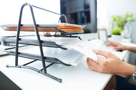 Close-up of a mans hand pulling files from office shelves. White collar job, digital shopping, office lifestyle, search success, enter login, password and credentials concept.