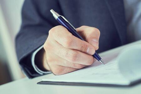 Mano dell'uomo d'affari in tuta che riempie e firma con il modulo di accordo di partnership con penna blu ritagliato per riempire il primo piano Corso di formazione manageriale, alcuni documenti importanti, concetto di ambizione del team leader.