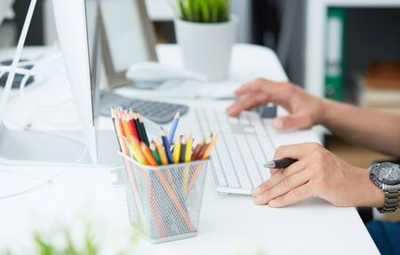 Close-up of mans hands typing on keyboard. White collar job, digital shopping, office lifestyle, search success, enter login, password and credentials concept. Modern office at background. Фото со стока