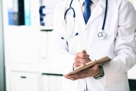 Male doctor in white coat on duty writes information with pen in clipboard closeup. Selective focus. Health and medical concept.