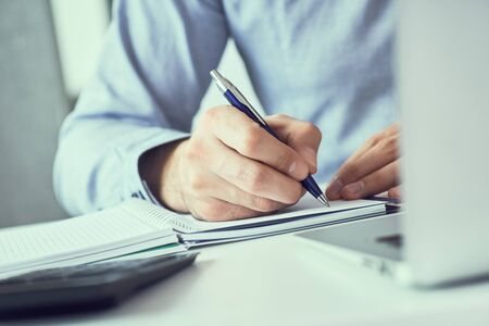 Businessman hand writing note on a notebook. Business man working at office desk. Male office worker writes information in a notebook.