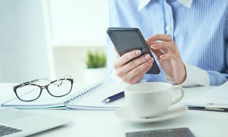 Hand of businesswoman using smartphone at office closeup. Business, technology and people concept. Desktop with lots of office supplies in the foreground.