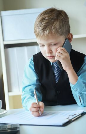 Little executive businessman boss boy making notes and talks on the phone and making notes sitting at the desk with laptop in office. Concept of early financial education Фото со стока