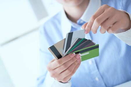 Woman hands holding various credit cards and making choice with another hand close-up. Фото со стока