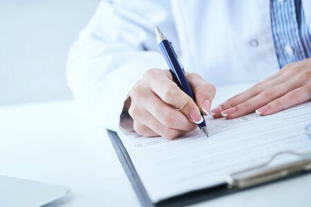 Female medicine doctor hand holding silver pen writing something on clipboard closeup. Lot of paper work in medicine. Ward round, patient visit check, medical calculation and statistics concept.
