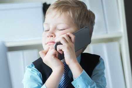 Little confident executive businessman boss boy in office talks on the phone sitting at the desk with laptop. Boy playing boss. Concept of early financial education.