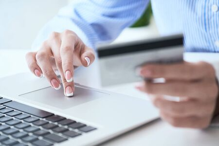 Female hand holding credit card and typing numbers on laptop keyboard while sitting at office table. Online loan payment concept. Selective focus.