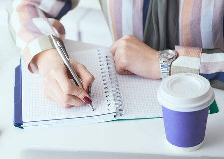 Business woman hands making notes with silver pen in office background. Business finance savings loan and credit concept. Фото со стока