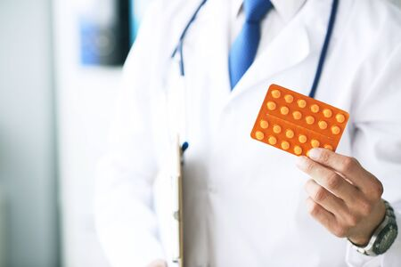 Close up of man hand holding pills or tablets in orange blister. Pharmaceuticals pills, seasonal disease prevention, medicine and healthcare concept.