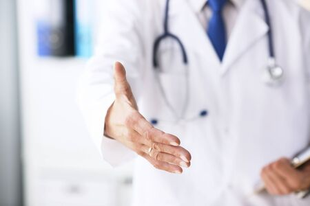 Male medicine doctor hold pad and give arm to shake in office closeup. Friend welcome introduction or thanks gesture. Work examine patient congratulation help exam teamwork deal concept.