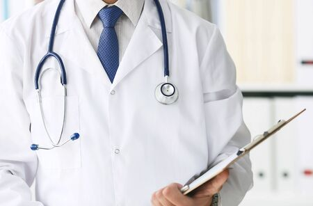 Close-up of clipboard with blank paper in medical doctor hand. Male doctor listens to the patient holding a clipboard with documents for hospitalization. Фото со стока