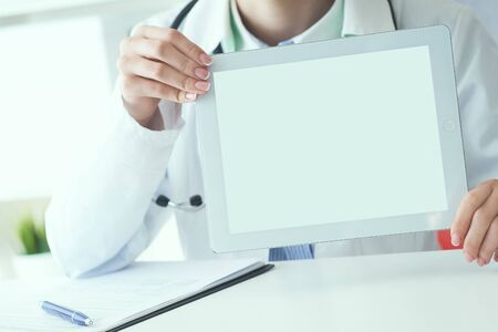 Middle section of female medicine doctor shows tablet computer with white screen. Contact information exchange, introducing gesture at formal meeting concept