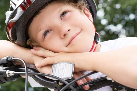 Small Caucasian boy cyclist in protective helmet put his head on the handlebar of the bike posing for the camera. a Boy rests during cycling in park on summer day. Weekend activity. Фото со стока