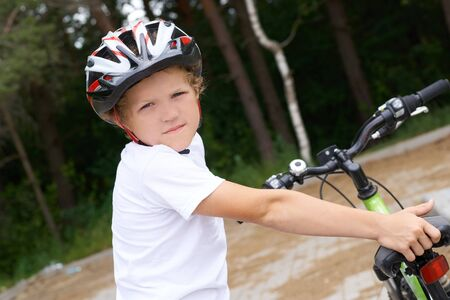 Small Caucasian boy in protective helmet stands leaning on the bike posing for the camera. Teenager ready to ride bicycle in park on summer day. Weekend activity.