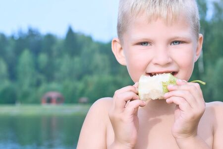 Little Caucasian blonde boy eating an pear on a hot summer day at the beach.