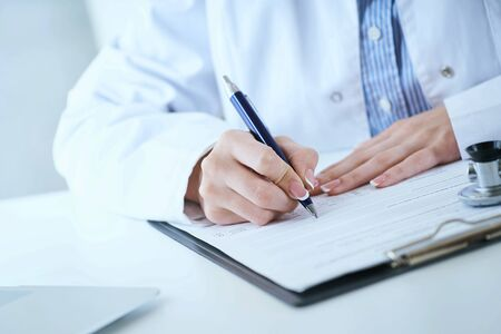 Female medicine doctor hand holding silver pen writing something on clipboard closeup.. Ward round, patient visit check, medical calculation and statistics concept.