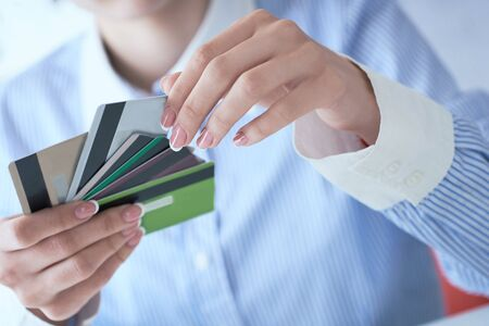 Woman hand holding various credit cards and making choice with another hand close-up. Фото со стока