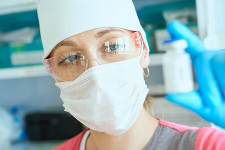 Young woman doctor dressed in mask, glasses and hat holds bottle of medicine for solution in the dropper in operating room before the surgery.