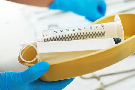 Syringe for gastric lavage in the hands of a nurse in the operating room. Nurse preparing medical instruments for operation.