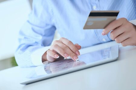 Close-up womans hands holding a credit card and using tablet pc for online shopping. Middle section of young businesswoman making online payments with credit card and tablet.